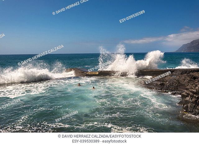 Unidentifiable Tourist swimming in coastline landscape in Puerto Santiago, Tenerife, Spain