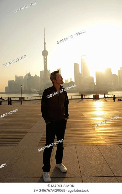 Mature man standing in front of city skyline at sunrise and smiling, Shanghai, China