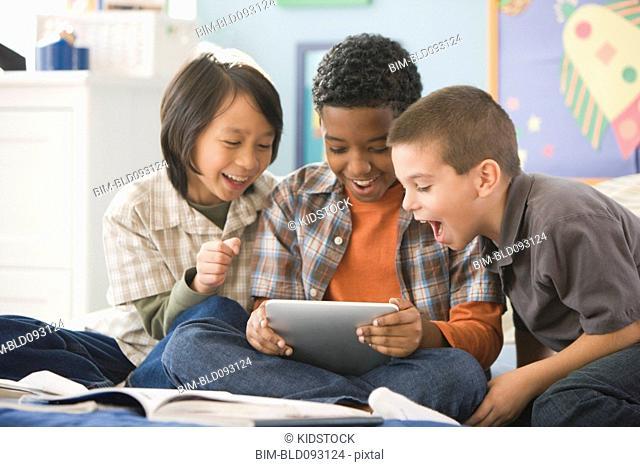 Boys using digital tablet together
