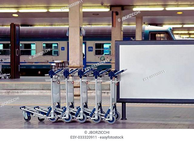 Luggage Carts in Railroad Station against a white billboard ideal to add text
