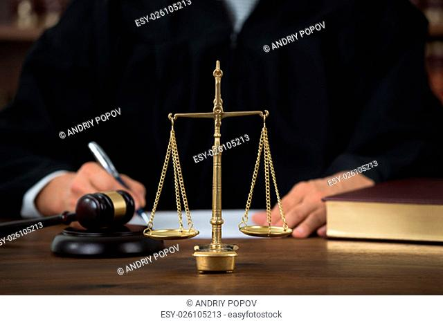 Law scales on table with judge writing in background at courtroom