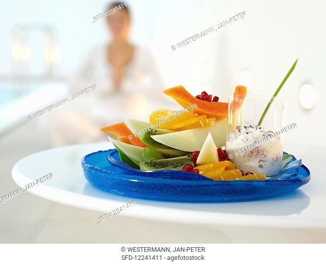 Fruit plate with papaya, kiwi, orange, pomegranate and grapefruit yoghurt