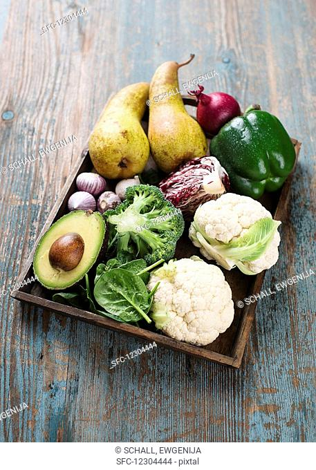 Various vegetables with pears on a wooden tray