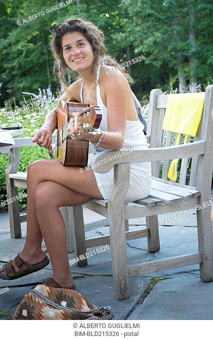 Caucasian woman playing guitar in backyard