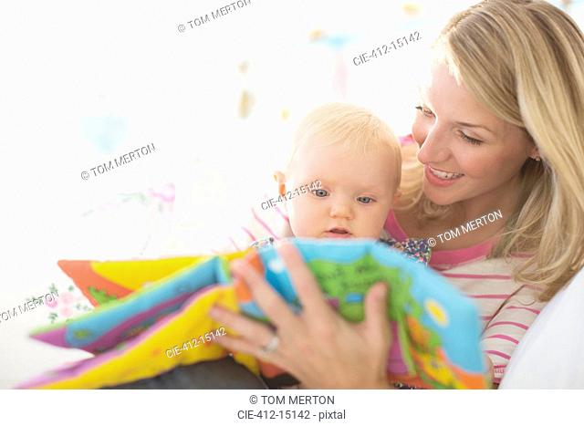 Mother reading to baby girl on sofa
