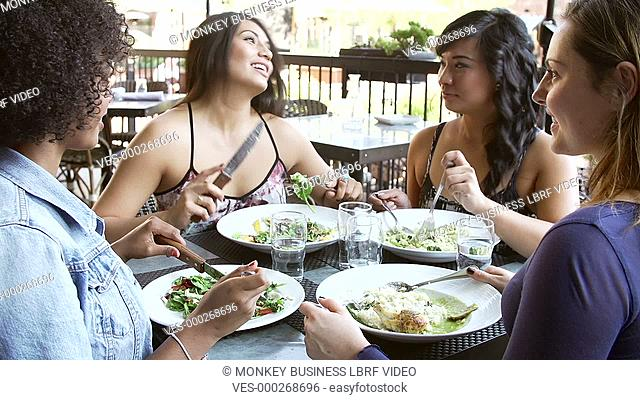Group of young women at outdoor restaurant enjoying meal and chat.Shot on Sony FS700 in PAL format at a frame rate of 25fps