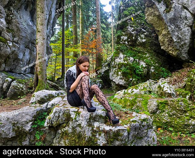 Young woman in nature sitting on big rock is sad Black clothing short minidress Black