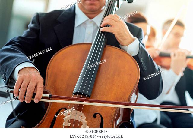 Professional cello player performing with other musicians, classical music symphony orchestra, unrecognizable person