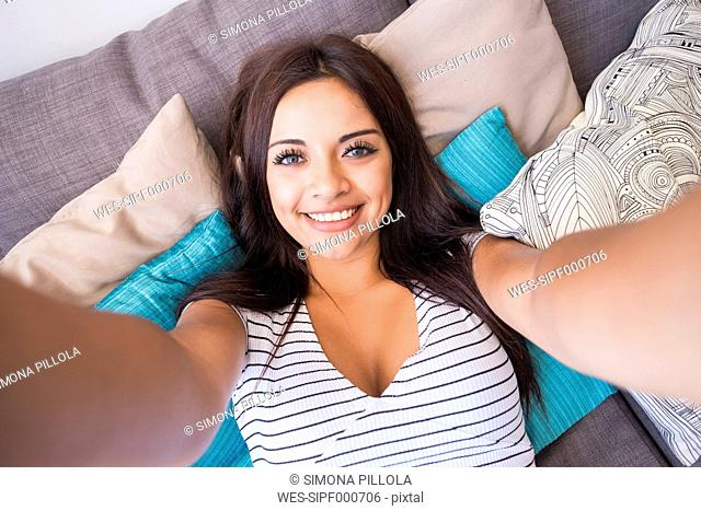 Portrait of smiling teenage girl lying on the couch taking selfie with cell phone