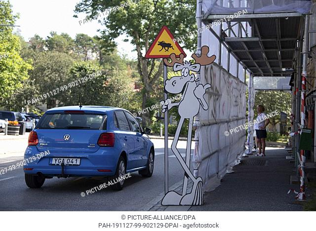 "11 July 2019, Sweden, Strömstad: A car drives past a cardboard moose in Strömstad. He's holding onto a warning sign for """"Beware Moose"