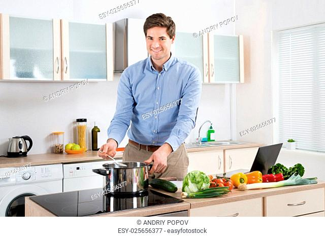Young Handsome Man Cooking Food In Kitchen At Home