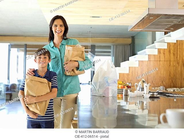 Mother and son holding groceries in kitchen