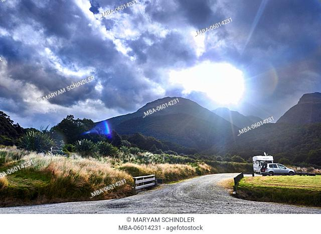 New Zealand, south island, the sun disappears behind mountains, atmospheric cloudy sky, parking lot, camper, car