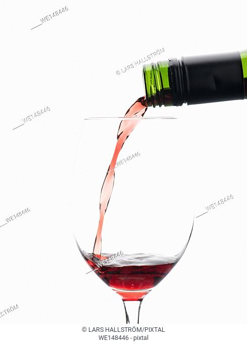 Red wine pouring from bottle in wineglass. Isolated on white background