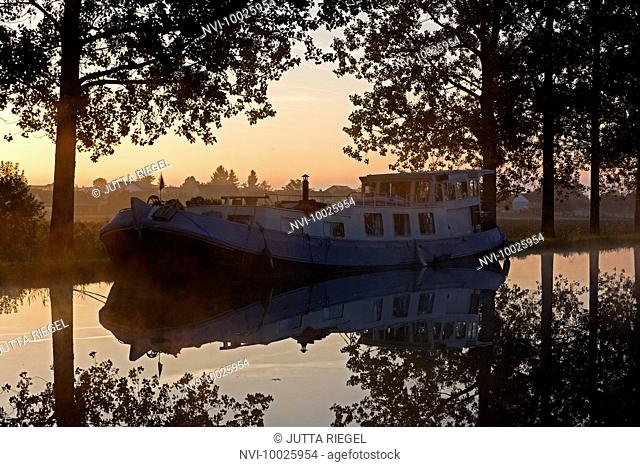 Boat in the evening light on river, France, Europe