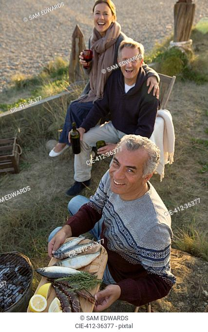 Portrait smiling mature friends barbecuing and drinking wine on beach