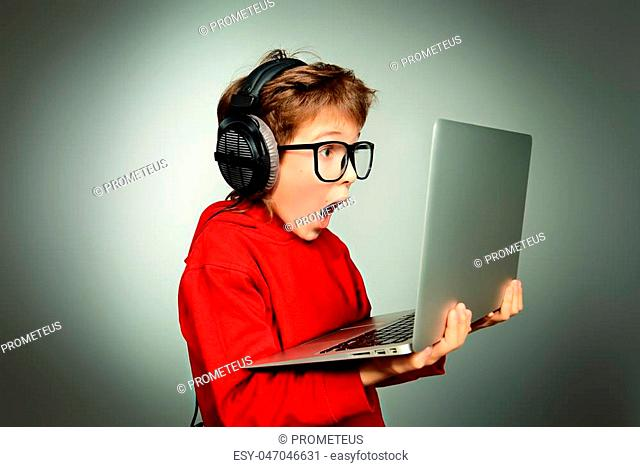 Cute boy in spectacles and headphones looking at his laptop monitor and shouting. Studio shot