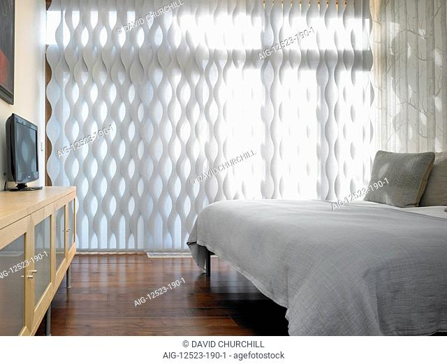 Garden House. Bedroom with dark wooden floor and honeycomb curtains