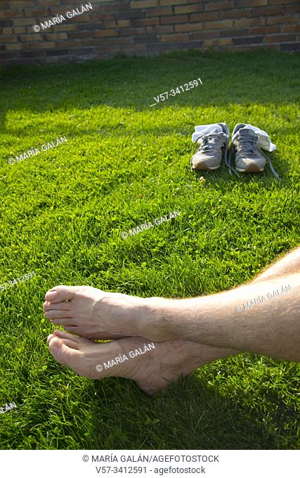 Barefoot man taking a rest on the grass