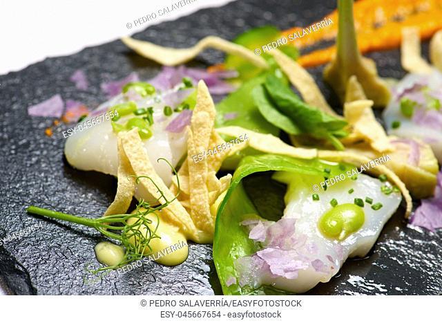 Marinated scallops served on a black slate