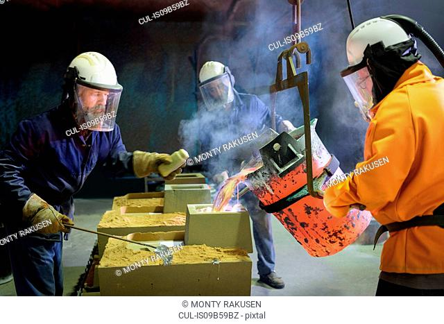 Workers pouring molten aluminium alloy into mould in precision casting factory