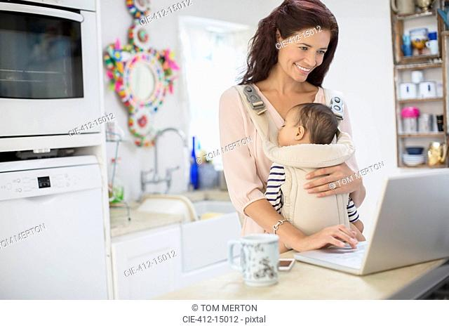 Mother holding baby boy and using laptop in domestic kitchen