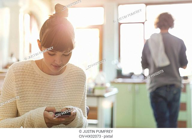 Young woman texting with cell phone in kitchen