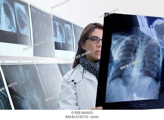 Hispanic doctor examining x-rays in hospital