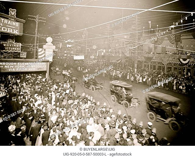 Cars in procession through the streets of Coney Island with American Flaf Banners draped on every building and attracting huge crowds