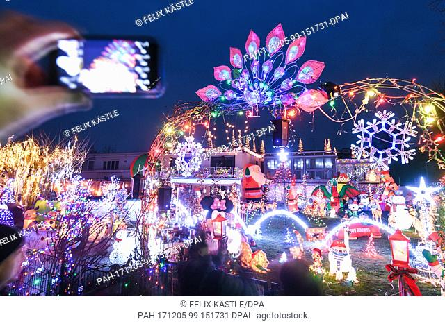 Dozens of illuminated Christmas figures and motives, as well as thousands of lights fill the front garden of a house while music completes the experience for...