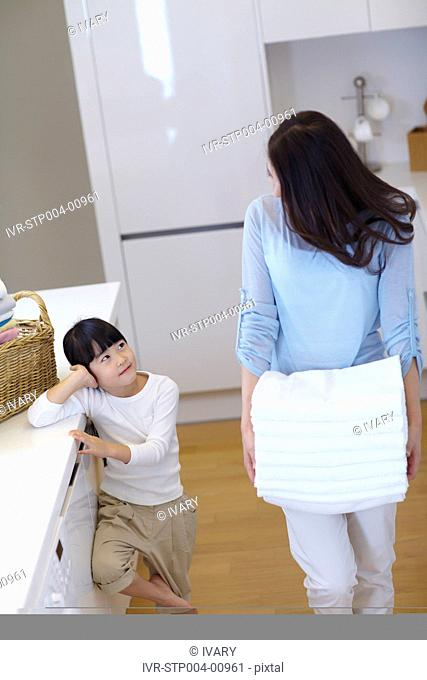 Daughter And Mother Carrying Stack Of Towels