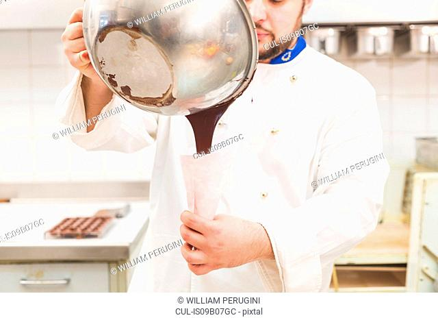 Chef pouring chocolate from mixing bowl into piping bag