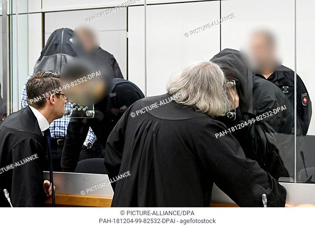 04 December 2018, Lower Saxony, Celle: A defendant talks to his defender Michael Murat Sertsöz (3rd from right). On the left
