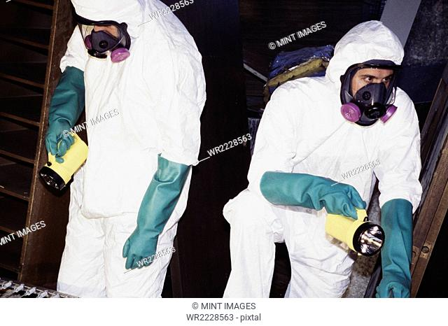 Two men wearing protective clean suits and breathing masks