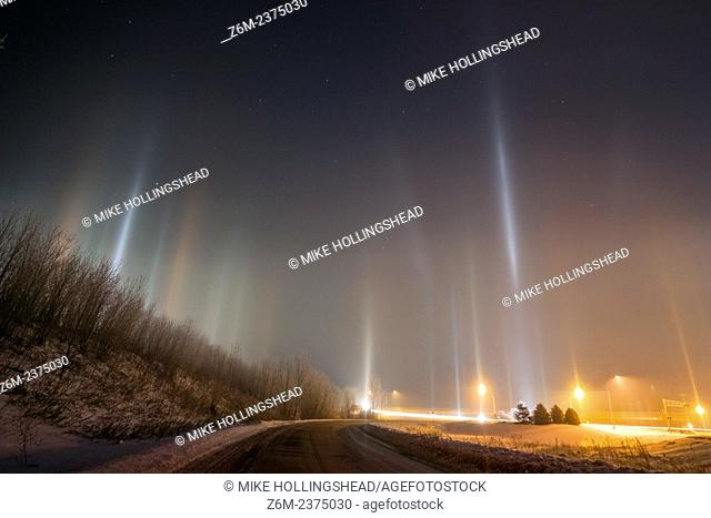 Arctic air combines with river steam and a corn milling plant's steam to produce light pillars, thanks to ice crystals floating in the air from the steam...